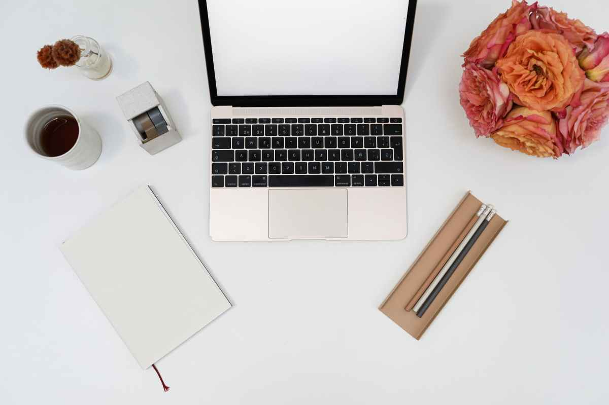 a laptop on a white desk surrounded by coffee, a notebook, pencils, and flowers
