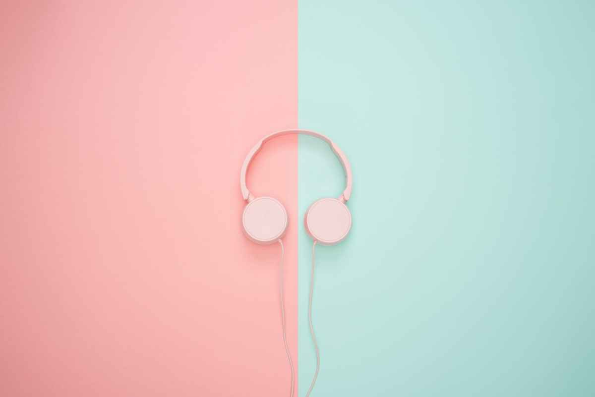 A pair of pink corded headphones on pink and teal wall