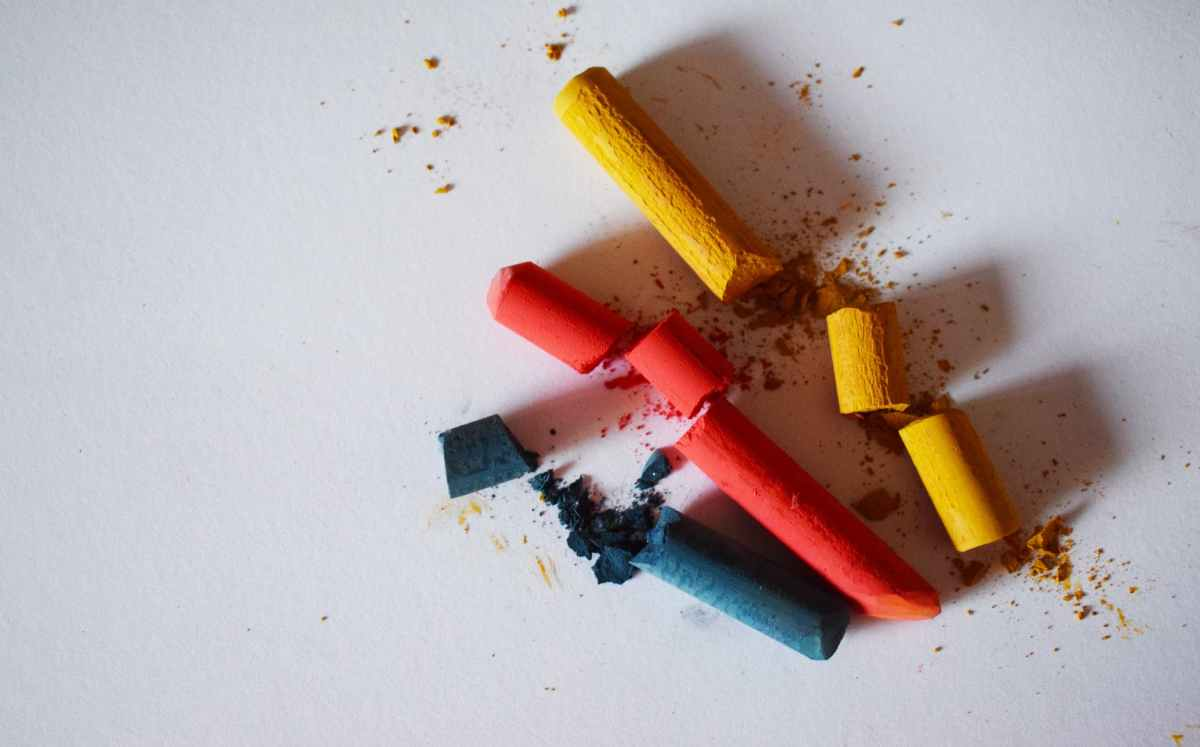 blue red and yellow chalk broken into pieces on a white background