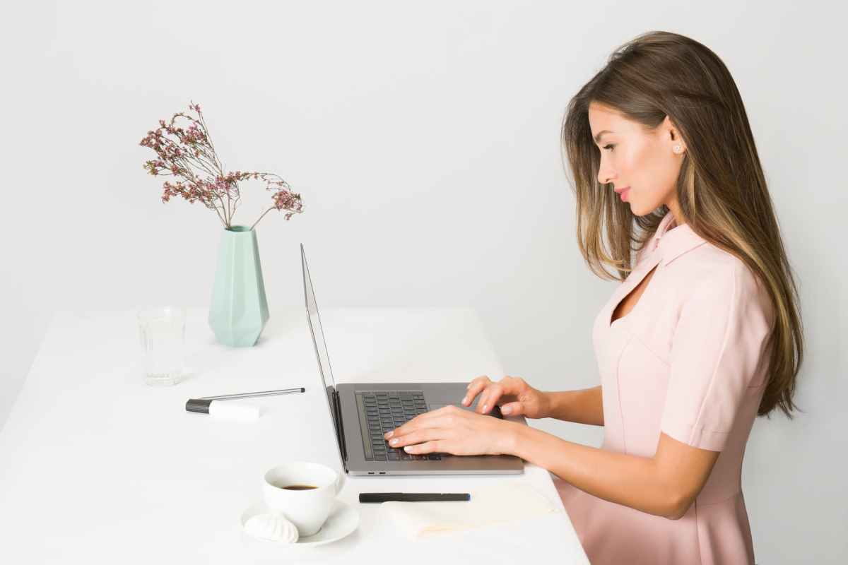 woman in a pink dress sitting at an open laptop, beside a vase of dried flowers and a cup of coffee.