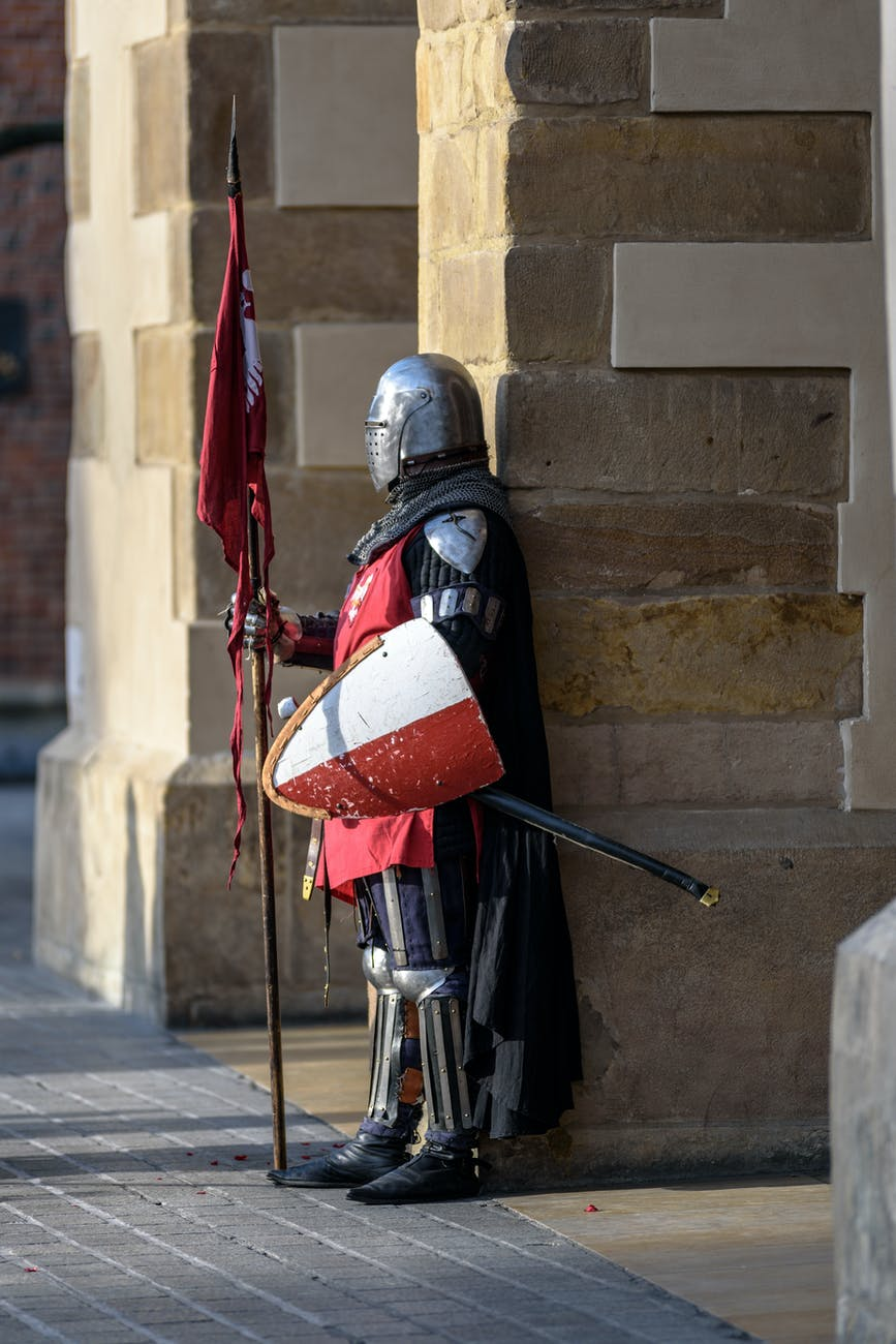 A person in a suit of armor holds a shield at their side with one hand, and a jousting instrument with the other.